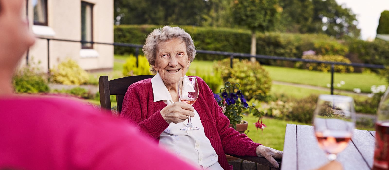 lady in garden drinking with neighbour